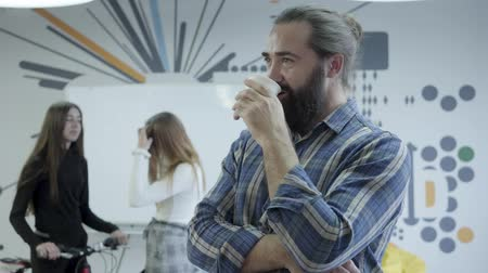 beardie : Positive beardie in checkered shirt drinking coffee looks back at his female colleagues, chatting in the background. The man is smiling. Friendly relationship in the office
