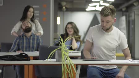 нетбук : The concentrated young man in white t-shirt finish his work with the laptop and walks away in the office. The man and woman kneading their necks, girl making massage to beardie in the background Стоковые видеозаписи
