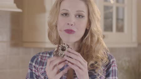 palce : Young beautiful blond woman greedily eating donut and licking her fingers Dostupné videozáznamy