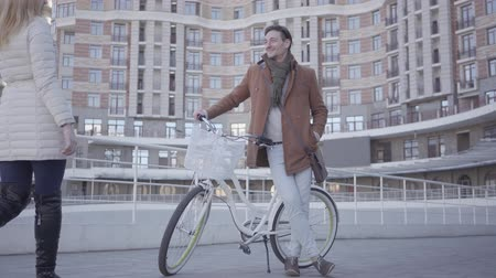 optimistický : Handsome serious man in brown coat and light blue jeans standing with his bicycle in the city in front of large building. Young blong woman comes hugs the man. Happy couple has a date