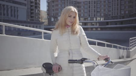 ciclismo : Portrait pretty blond woman in warm white jacket standing at the city street with bicycle looking in the camera touching her hair. Leisure of young city dweller. Active lifestyle. Slow motion