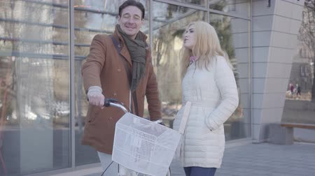 支出 : Handsome tall man holding his bicycle talking with pretty blond woman in warm jacket. Positive couple chatting standing near the mall in the city. Cute couple spending time outdoors