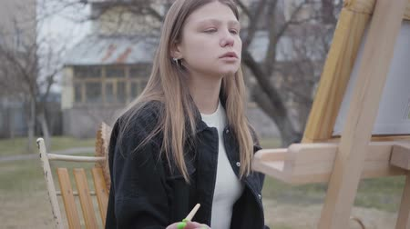 курение : Portrait pretty young smoking girl painting on canvas while sitting in the backyard outdoors. Successful artist passionate about his occupation. Real people series.