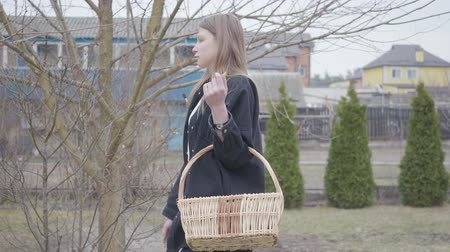 proutěný : Cute young woman walking with the wicker basket of walnuts holding brush in hand. Attractive artist in casual clothes walks through the garden. Leisure of country girl. Side view