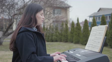 dizgi : A beautiful brunette girl plays on a synthesizer and sings while sitting in the backyard outdoors. Young successful woman is keen on occupation. Real people series.