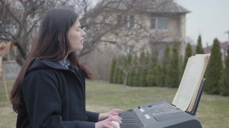 dizgi : A successful beautiful brunette girl plays on a synthesizer and sings while sitting in the backyard outdoors. Young successful woman is keen on occupation. Real people series. Stok Video