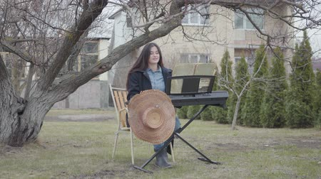 dizgi : Successful talented beautiful brunette girl playing synthesizer and sings while sitting under the tree in the backyard outdoors. Romantic, meditation, electronic music Stok Video