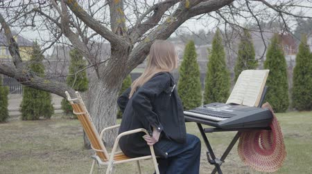 dizgi : Young woman comes and sits at keyboard instrument outdoors, preparing to play. Notebook with notes is on a stand in front of the girl. Female musician in casual closing plays synthesizer