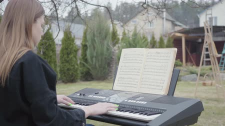 dizgi : Professional cute pianist play classical piano music on the synthesizer in the backyard. Real people series. Stok Video