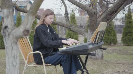 dizgi : Professional cute female pianist play classical piano music on the synthesizer in the backyard. Real people series.