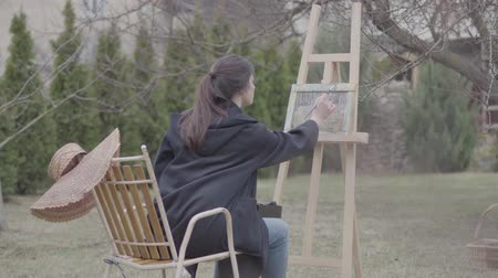 dessin paysage : Skilled artist paints on the canvas in the backyard. Beautiful enthusiastic girl engaged in creativity. Inspiration. Talent. Vidéos Libres De Droits