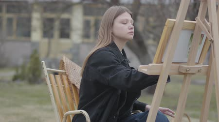 şövale : Concentrated woman painter sitting in front of wooden easel drawing a picture. Handsome man comes and covers eyes of the artist. Creativity, self-expression, love concept. Art academy or drawing school.