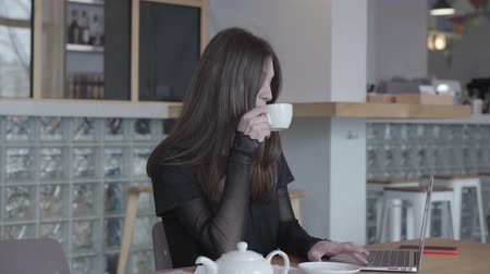 ネットブック : Beautiful successful busy girl in a black strict dress is looking at the papers while sitting at the table next to the laptop. Business woman is resting studying documents and drinking tea or coffee.