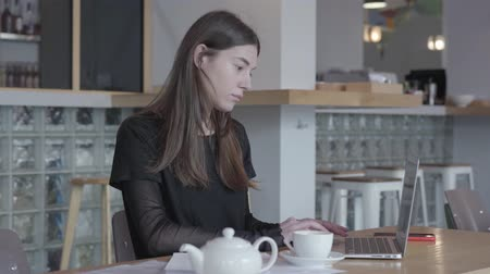 remotely : Attractive young woman in black dress sitting at the table in modern cafe working on her netbook. White teapot and cup are at the table. Lady is working in cafe. Remote work. Freelancer. Stock Footage