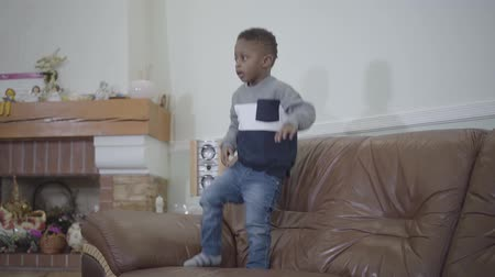 afro americana : African american small cute child boy jumping on sofa on the background of cozy living room. Relationship mom and son. A happy family. Slow motion.