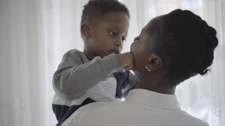 blúz : African american stylish woman in white blouse taking on hands her funny playful child boy in cozy living room. Relationship mom and son. A happy family.