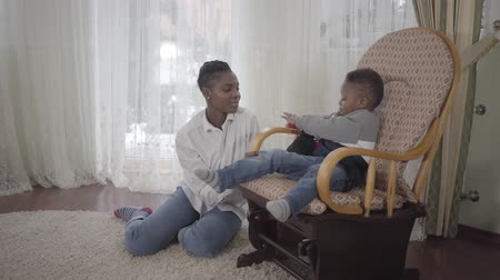 szomjúság : Joyful cute african american woman playing with her small cute and funny son sitting on a rocking chair in living room. Relationship mom and son. A happy family. Stock mozgókép