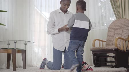 egyéniség : American african woman searching something on cell phone and her small cute son interested in cozy living room. Relationship mom and son. A happy family. Stock mozgókép