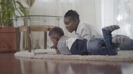 desobediente : African american woman working on the laptop lying on the carpet and her little cute son come to her with toy. Relationship mom and son. A happy family. Freelancer. Remote work. Disobedient child.