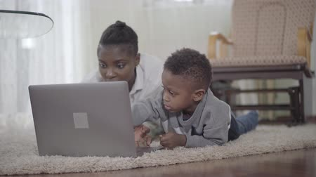 ayrılmak : Portrait happy African american woman with her cute son lying on the carpet and searching something in internet on the laptop. Relationship mom and son. Freelancer. Remote work. Stok Video