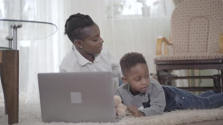 afro amerikai : Portrait happy African American woman with her cute son lying on the carpet and searching something in internet on the laptop. Relationship mom and son. Freelancer. Remote work. Disobedient child.
