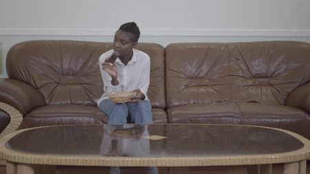 fome : Attractive african american woman sitting on the sofa and was going to eat snack, but her small child come to have fun Vídeos