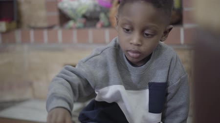 fireside : Portrait of small african american child boy focused playing and having fun with toys in living room. Stock Footage