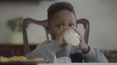 cálcio : Portrait of cute african american child boy sitting by the table and drinking milk from the glass on the background of cozy living room
