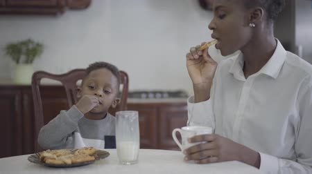 cálcio : Attractive african american woman sitting with her little son by the table eating cookies and drinking milk. Relationship mom and son. A happy family. Family healthy breakfast.