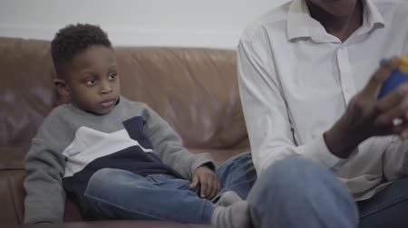 ayrılmak : Cute African american woman and her little cute son playing with toys sitting on the couch in cozy living room. Relationship mom and son. A happy family. Stok Video