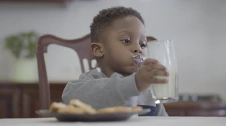 ailelerin : Portrait of funny african american child boy sitting by the table and drinking milk from the glass on the background of cozy living room