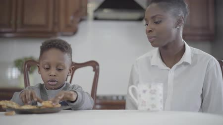 столовая : African american woman sitting with her little son by the table on the kitchen. Relationship mom and son. A happy family. Family healthy breakfast.