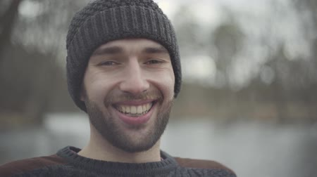 unrest : Portrait of a bearded confident smiling hipster in a warm hat standing outdoors. Man is relaxing on the weekend in the park.