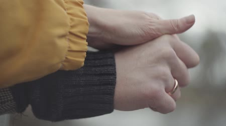 close cropped : Man and woman hold hands outdoors on the blurred background. Gold ring is on the man finger. Lovely couple in warm coats rest together in spring park Stock Footage