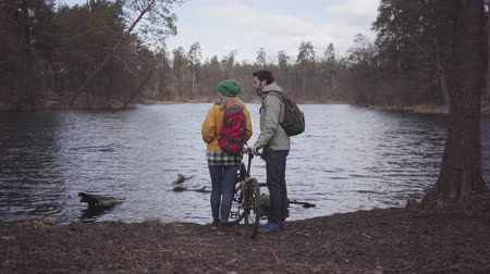 feed back : Young couple of tourists standing on the riverbank with backpacks on their backs. The man holds the bicycle and woman in bright yellow jacket feeding the duck. Lovers rest outdoors. Back view