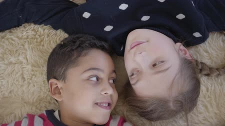 бежевый : Cute african american boy and blond caucasian girl lying on the floor on the beige fluffy carpet and looking at each other with love. Top view. Rest of happy children. Стоковые видеозаписи