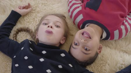 베이지 색의 : Portrait african american boy and blond caucasian girl lying on the floor on the beige fluffy carpet and looking in camera showing their tongues. Leisure of funny kids. Top view. Rest of happy childre