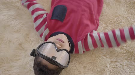 paintball : Portrait of little african american boy lying on the floor on the beige fluffy carpet with ski goggles on his eyes close up. Funny boy have a fun. Rest of happy children.