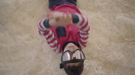 paintball : Portrait of adorable african american boy lying on the floor on the beige fluffy carpet with ski goggles on his eyes close up. Funny boy have a fun. Rest of happy children.