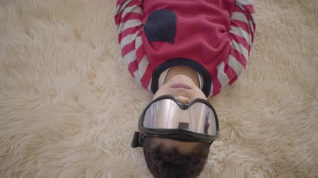 paintball : Close up portrait of adorable african american boy lying on the floor on the beige fluffy carpet with ski goggles on his eyes close up. Funny boy have a fun. Rest of happy children.