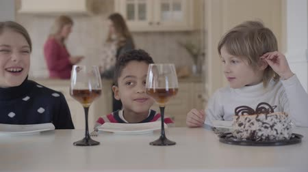 atender : Three funny kids sitting at the table with small cake and wine glasses with juice. Two caucasian girls and african american boy have fun together