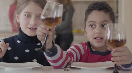 atender : Two kids sitting at the table at home. Caucasian blond girl and african american boy have fun together. The boy giving glass with juice to girlfriend. Leisure of two funny cute kids of different races