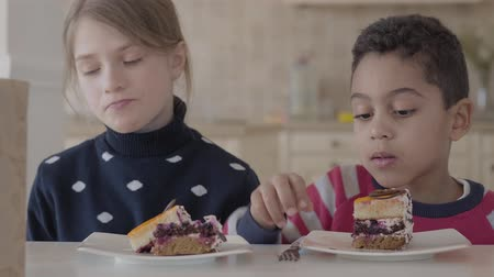 kekler : Happy kids eating cake while sitting at the table in the kitchen. Stok Video