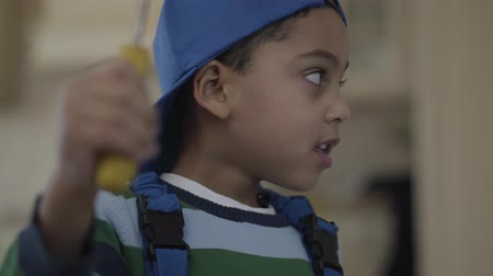 ремонтник : Cute little african american boy in blue uniform playing with screwdriver pretending he is repairer. The child involved in interesting game imitates an adult. Kid is in a playful mood