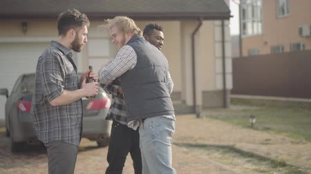 köszönt : Two caucasian and african american men standing in front of big house drinking beer. The third friend comes, men greet each other, hugging. Old friends have fun together