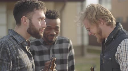beer house : Portrait of three caucasian and african american men standing in front of big house drinking beer. One guy finished his beverage, friends propose to share, laughing. Old friends have fun together. Stock Footage