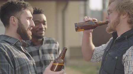 beer house : Portrait of three caucasian and african american men drinking beer outdoors. Old friends have fun together.