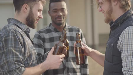 venir : Portrait of three caucasian and african american men standing in the backyard drinking beer. The men clink their bottles smiling. Old friends have fun together