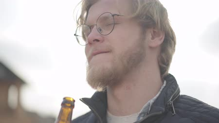 látszó el : Bearded man with glasses drinking beer and enjoying beverage outdoors. Guy tastes lager from bottle. Stock mozgókép