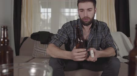чувствовать : Young bearded man sitting on the sofa takes empty beer bottle from the table and look at it with perplexity. The guy feels bad after hangover. Unhealthy lifestyle Стоковые видеозаписи